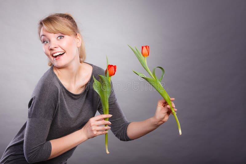 Шаловливая девушка имея потеху с тюльпанами цветков стоковое изображение