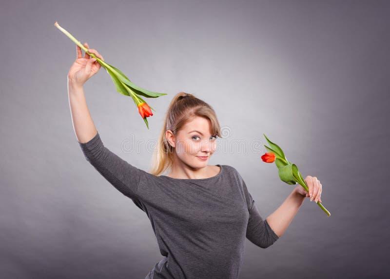 Шаловливая девушка имея потеху с тюльпанами цветков стоковое фото