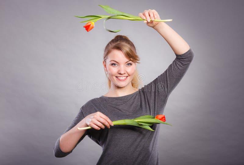 Шаловливая девушка имея потеху с тюльпанами цветков стоковые фотографии rf