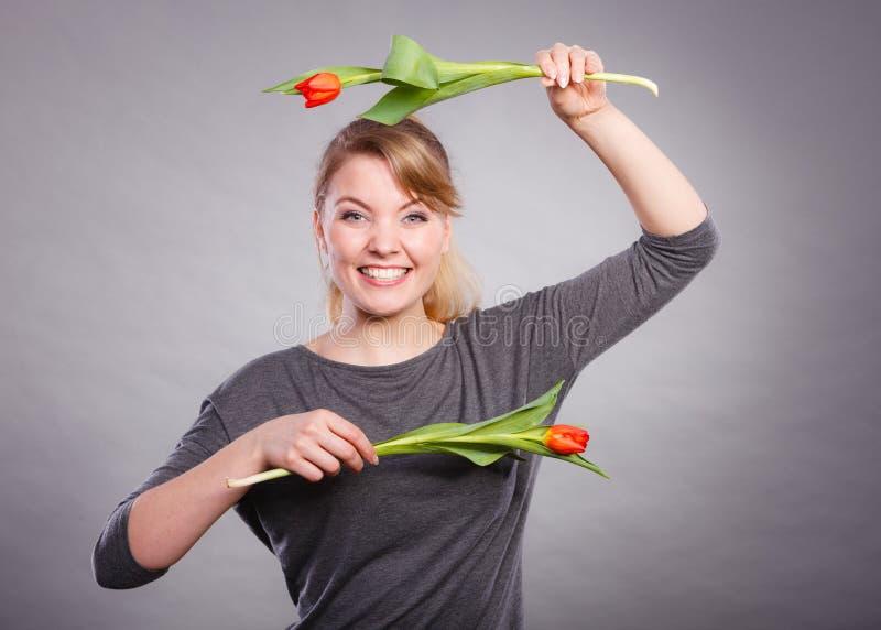 Шаловливая девушка имея потеху с тюльпанами цветков стоковая фотография