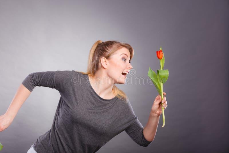 Шаловливая девушка имея потеху с тюльпаном цветка стоковая фотография rf