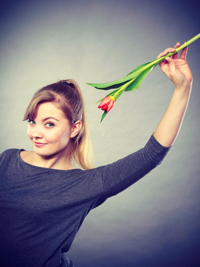 Шаловливая девушка имея потеху с тюльпаном цветка стоковое изображение