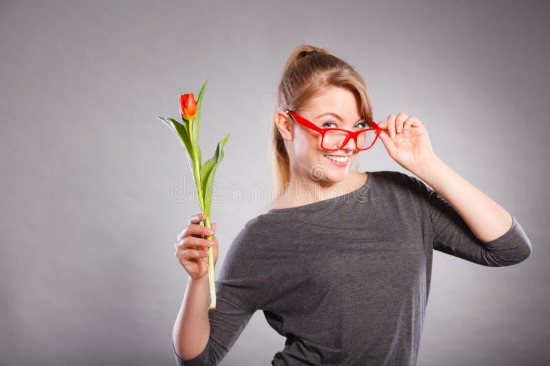 Шаловливая девушка имея потеху с тюльпаном цветка стоковое фото