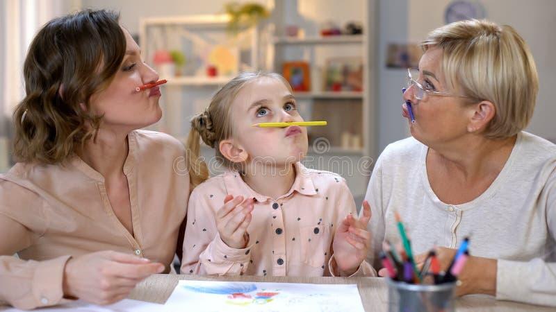 Шаловливая женщина с дочерью и внучкой держа карандаши как усик, потеха стоковая фотография rf