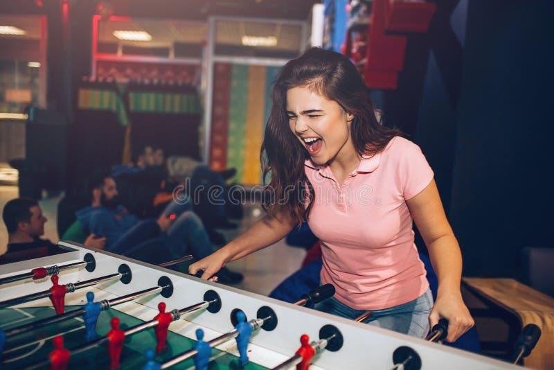 Шаловливый футбол таблицы игры молодой женщины в комнате Она клекот Модель радуется Молодые люди позади сидят и играют игры стоковое фото rf