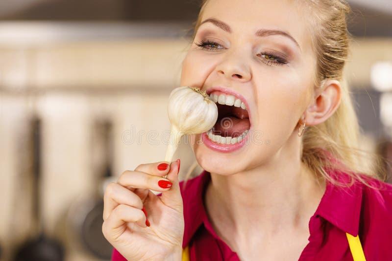 Шальная девушка есть овощ чеснока стоковые фото