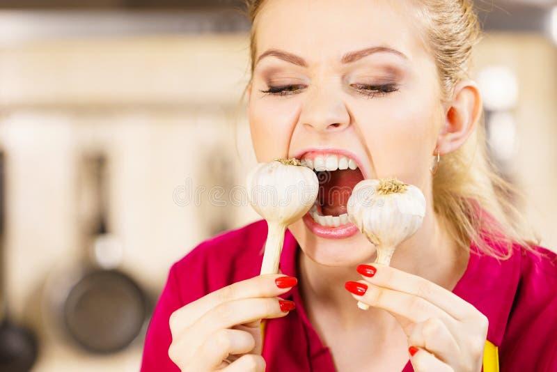 Шальная девушка есть овощ чеснока стоковые фотографии rf