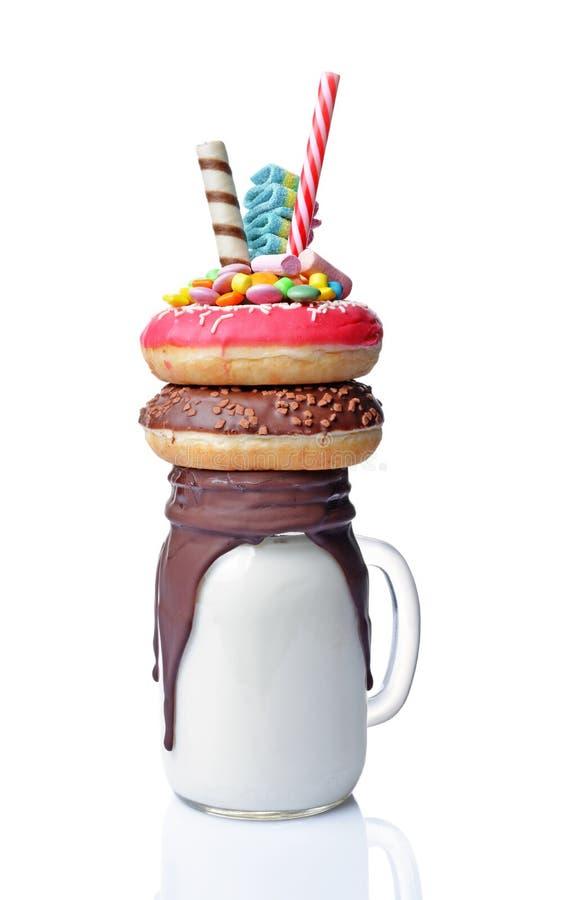 Шальной молочный коктейль с donuts пинка и шоколада, конфетой цвета и соломой в стеклянном опарнике стоковые изображения