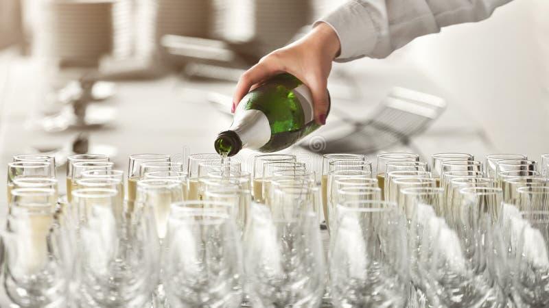 Шампанское кельнера лить в стекла на партии стоковое изображение rf