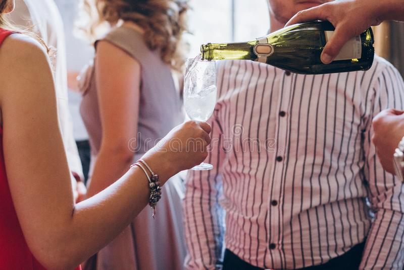 Шампанское кельнера лить в стекле элегантные люди держа glasse стоковая фотография