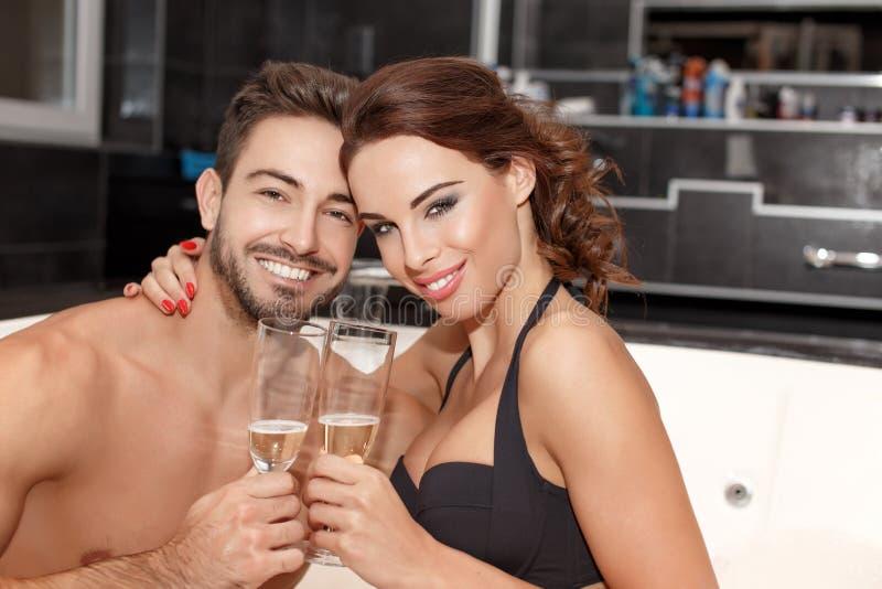 Шампанское молодых пар выпивая в джакузи стоковые изображения