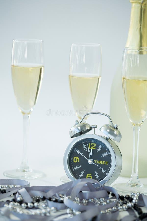 Шампань с будильником и стеклом на белой предпосылке стоковые фотографии rf