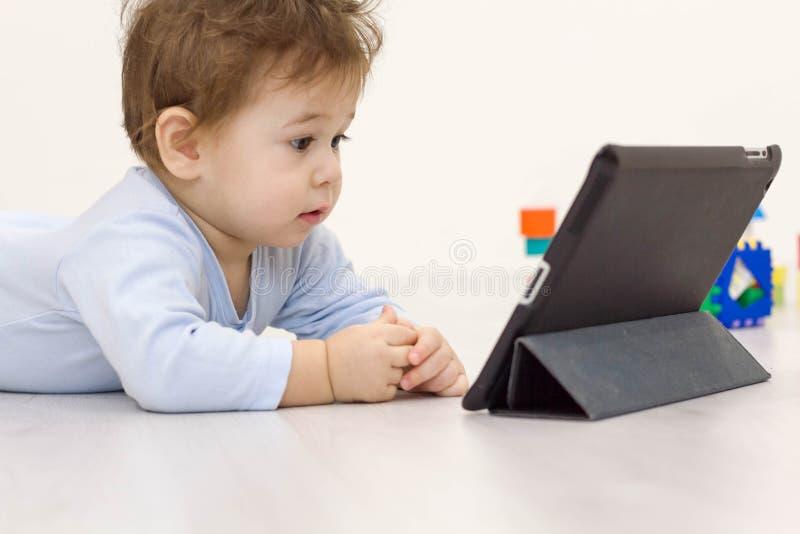 Шаржи девушки малыша наблюдая на ее планшете на заднем плане игрушек он ребенок не хочет сыграть стоковые изображения rf