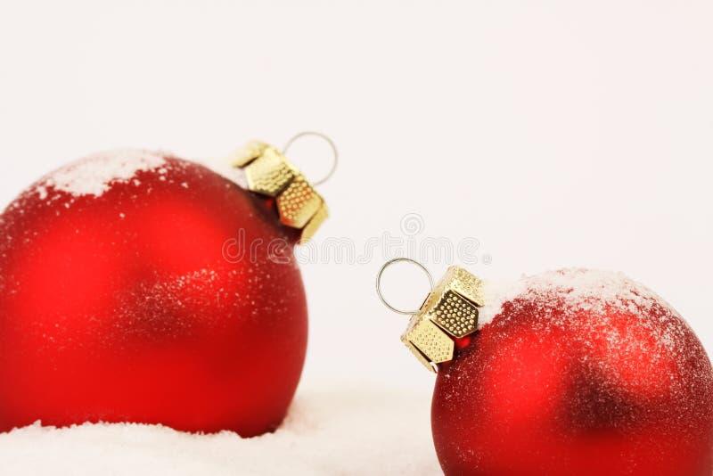 2 шарика снежных красных рождества матовых стоя на снеге на белой предпосылке стоковые фотографии rf