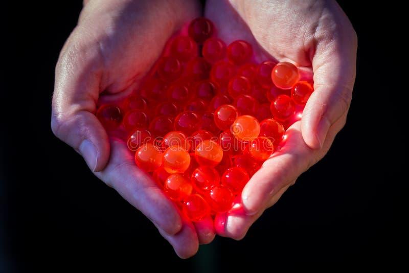 Шарики геля воды красные Небольшой шарик геля в руке Гель полимера Гель кремнезема Шарики красного гидрогеля Кристаллический жидк стоковое фото rf