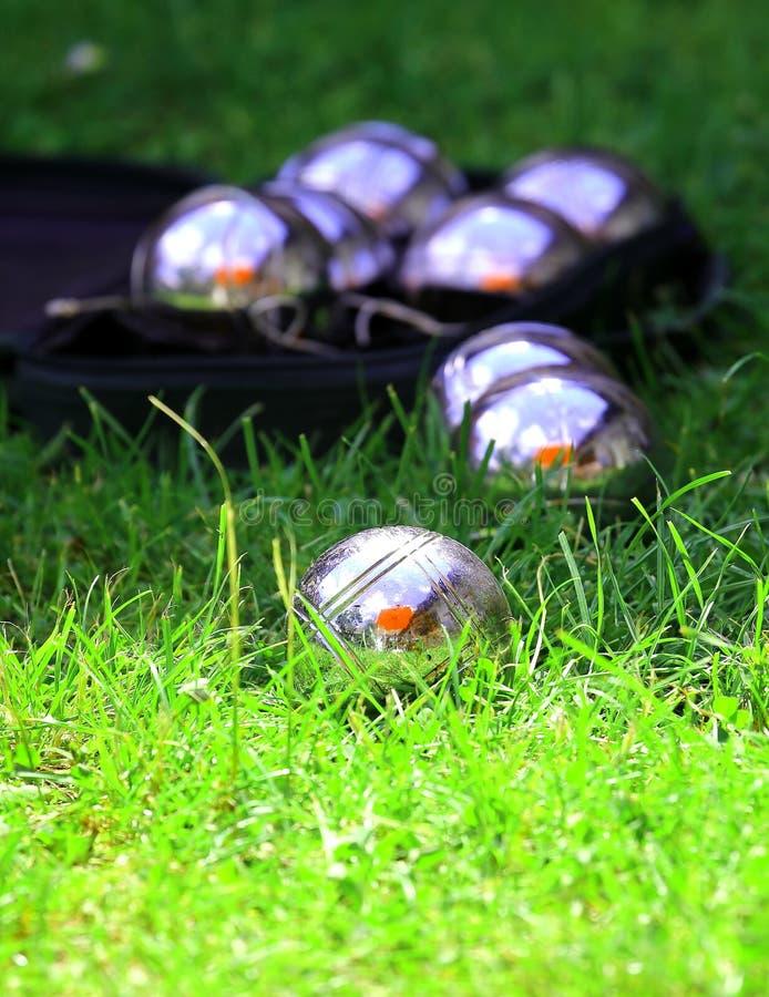Шарики игры в петанки в свежей зеленой траве стоковые изображения rf