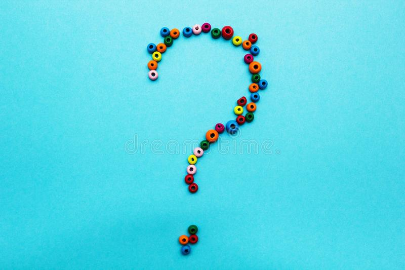 Шарики пестротканых детей, разбросанные на голубую предпосылку, вопросительный знак стоковые фото