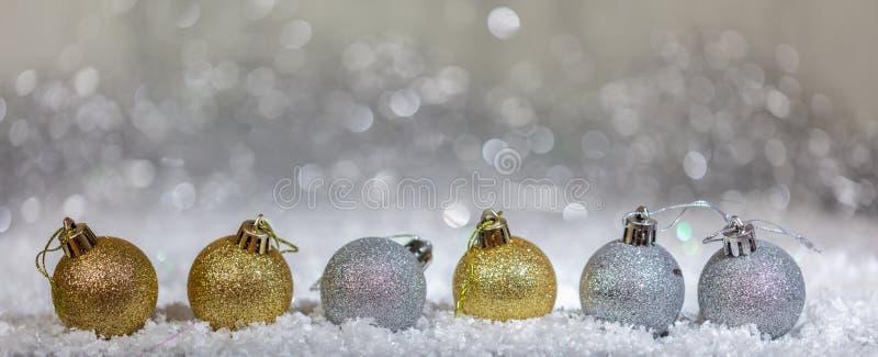 Шарики рождества, золотой и серебряный на снеге, абстрактной предпосылке светов bokeh стоковое изображение