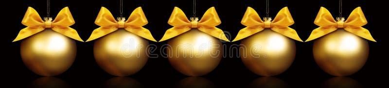 Шарики рождества золотые вися в черной предпосылке стоковое изображение