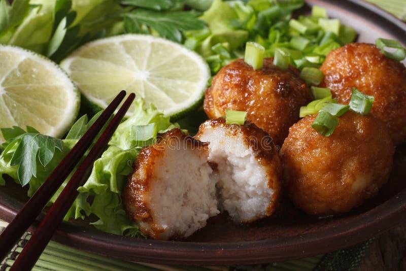 Шарики рыб с известкой и салатом на макросе плиты горизонтально стоковое фото