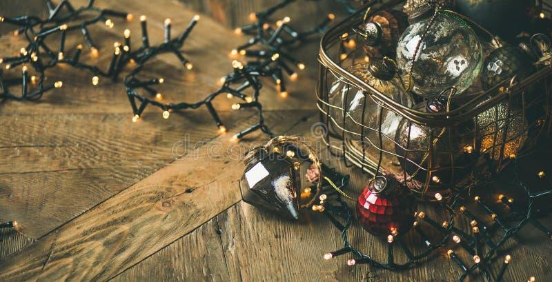 Шарики украшения рождества в гирлянде коробки и света, деревенской предпосылке стоковая фотография