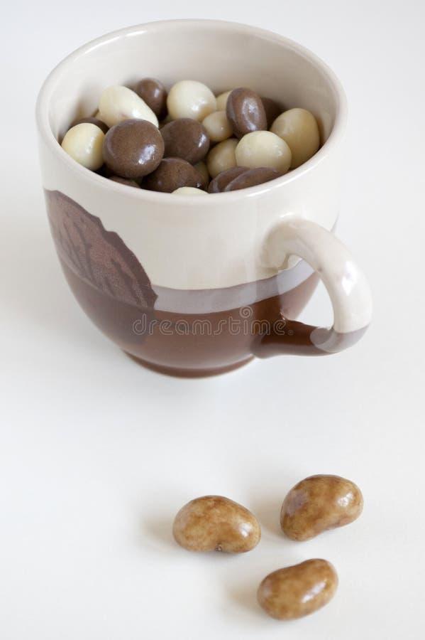 Шарики шоколада с гайками на светлой предпосылке стоковые фото
