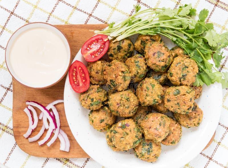 Шарики Falafel и свежие овощи на плите с sause стоковое фото