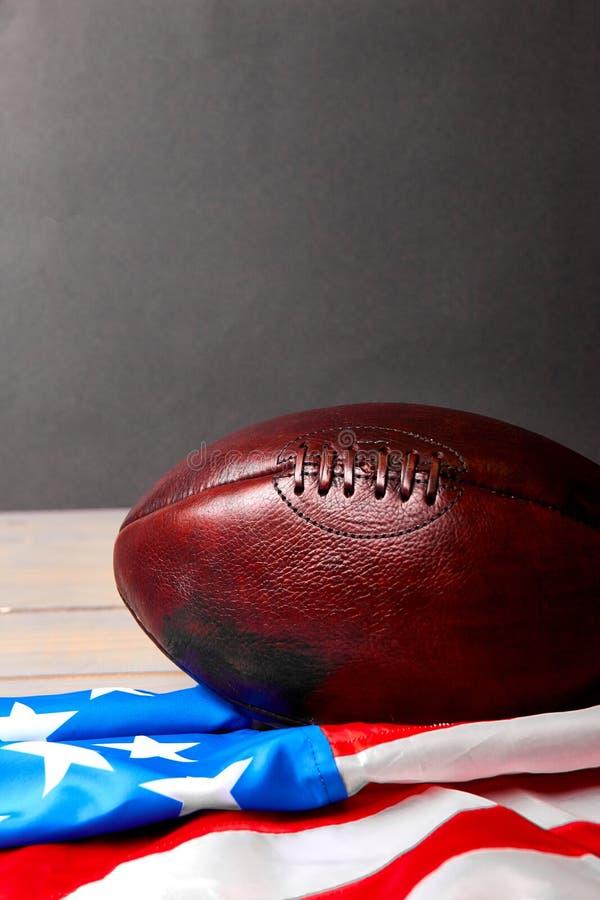 Шарик американского футбола и флаг государственного флага США стоковая фотография