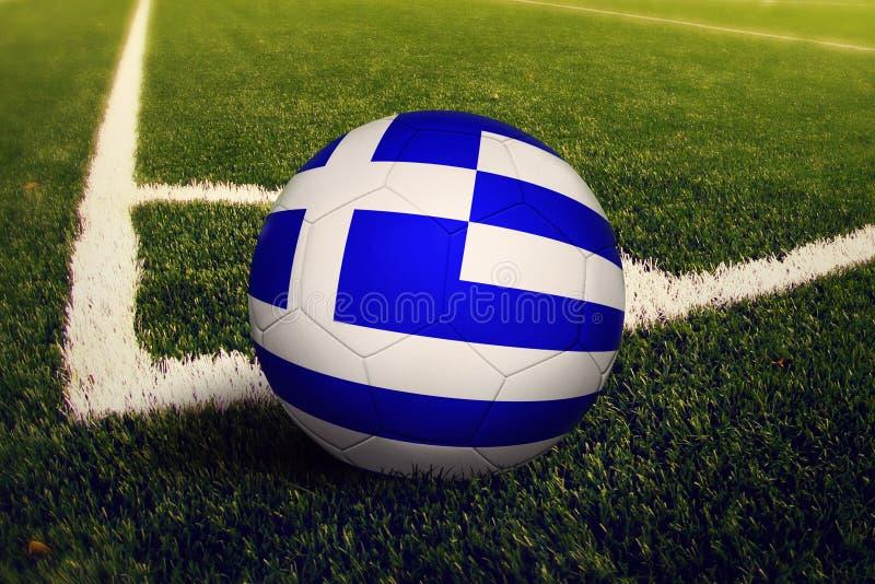 Шарик Греции на положении углового удара, предпосылке футбольного поля Национальная тема футбола на зеленой траве иллюстрация вектора