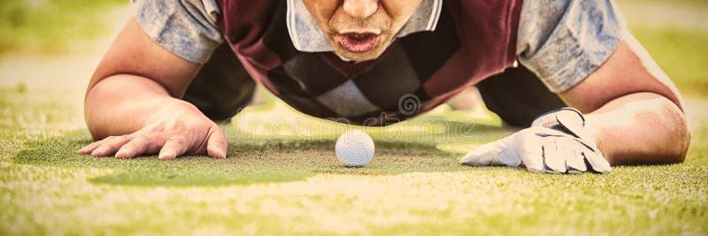 Шарик игрока в гольф дуя в отверстии стоковые изображения
