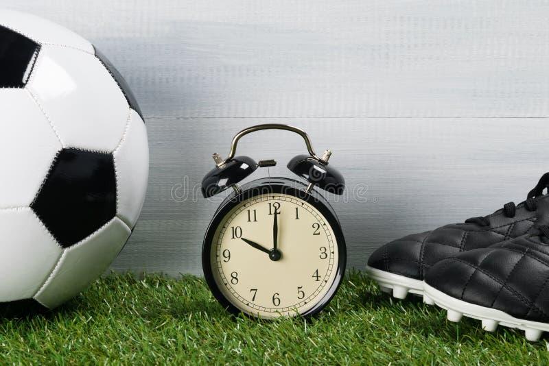 Шарик и кожаные ботинки для играть футбол рядом с часами на зеленой предпосылке травы стоковые изображения rf