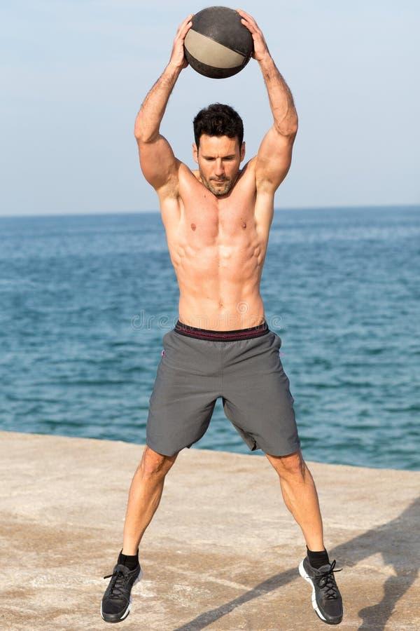 Шарик медицины атлетического человека бросая стоковая фотография