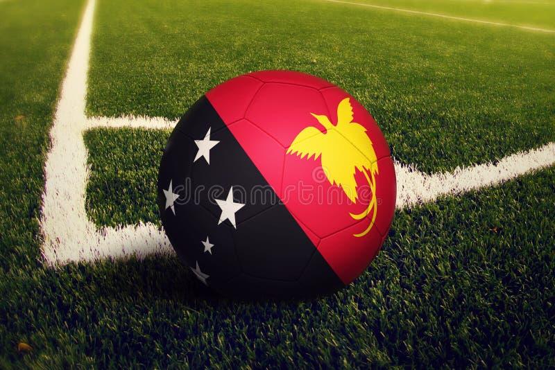 Шарик Папуаой-Нов Гвинеи на положении углового удара, предпосылке футбольного поля Национальная тема футбола на зеленой траве стоковая фотография rf