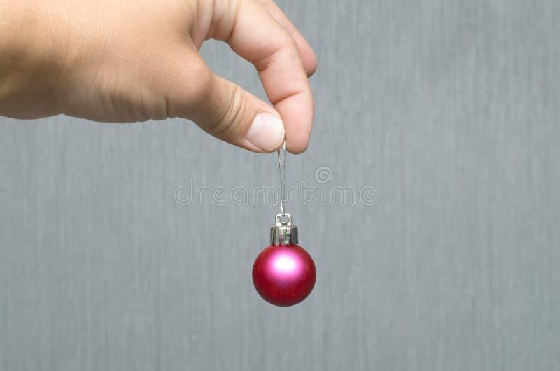 Шарик рождества в руке на серебряной стене стоковая фотография rf