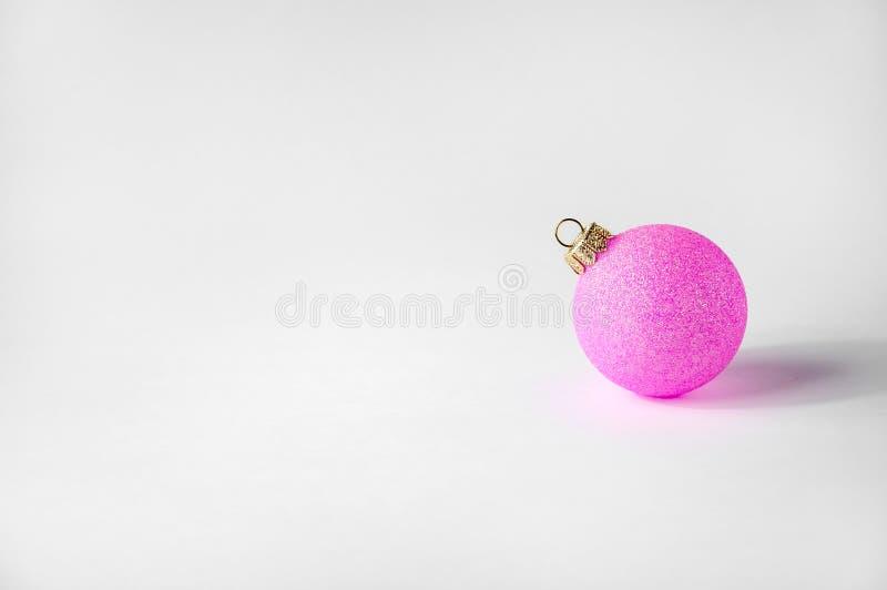 Шарик рождества розовый на светлой предпосылке Минимальный состав праздника Нового Года знамена скопируйте космос стоковое фото rf