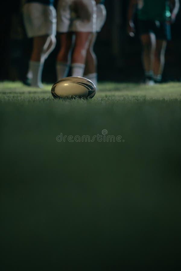 Шарик рэгби на траве с командами в предпосылке стоковое фото rf