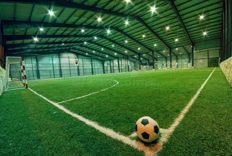 Шарик футбола на зеленой траве в крытой спортивной площадке
