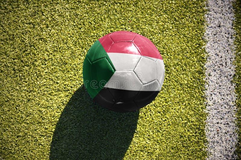 Шарик футбола с национальным флагом Судана лежит на поле стоковые фотографии rf