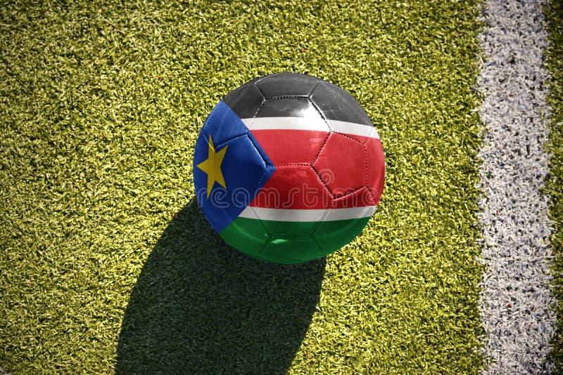 Шарик футбола с национальным флагом южного Судана лежит на поле стоковая фотография rf