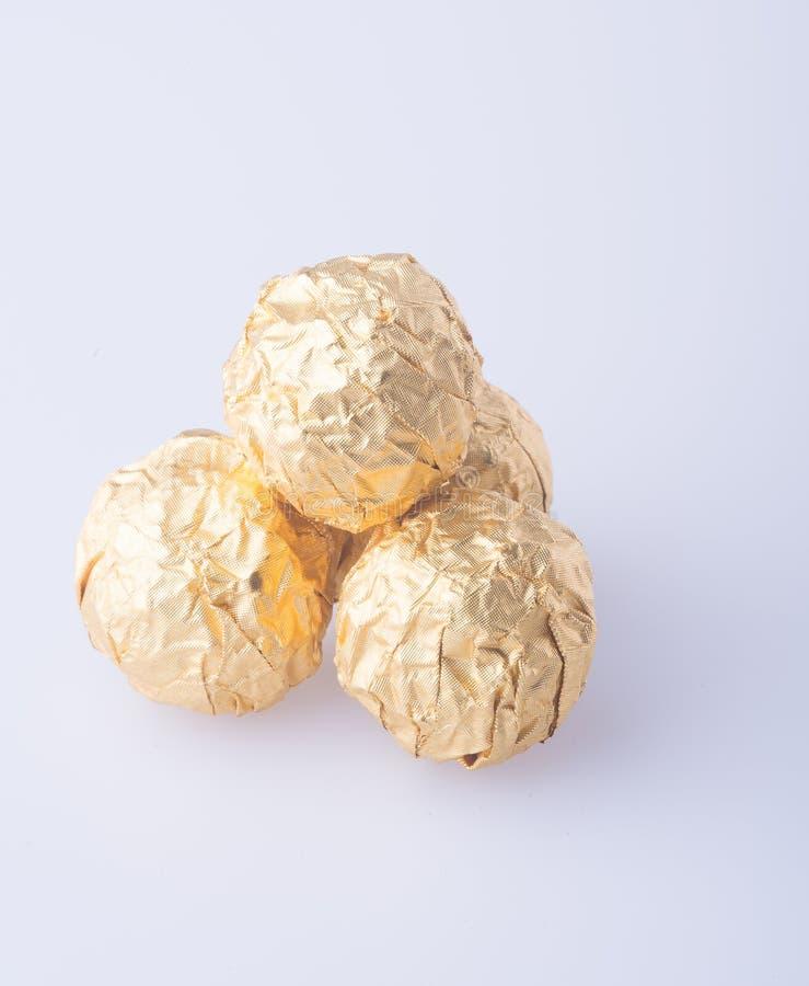 Шарик шоколада в бумаге сусального золота на предпосылке стоковое фото rf
