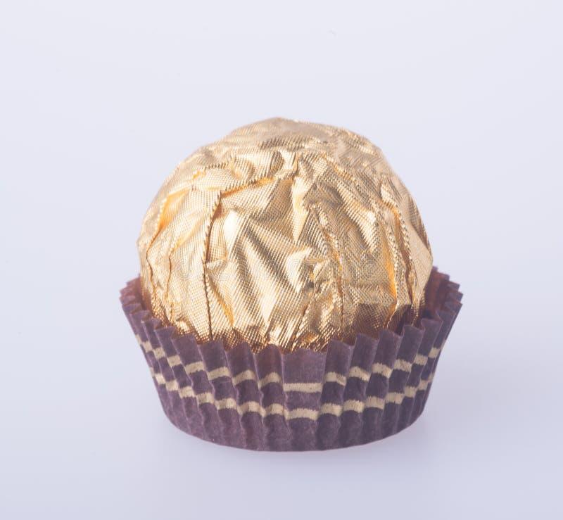 Шарик шоколада в бумаге сусального золота на предпосылке стоковое изображение rf
