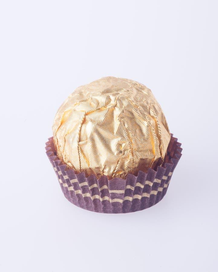 Шарик шоколада в бумаге сусального золота на предпосылке стоковое изображение