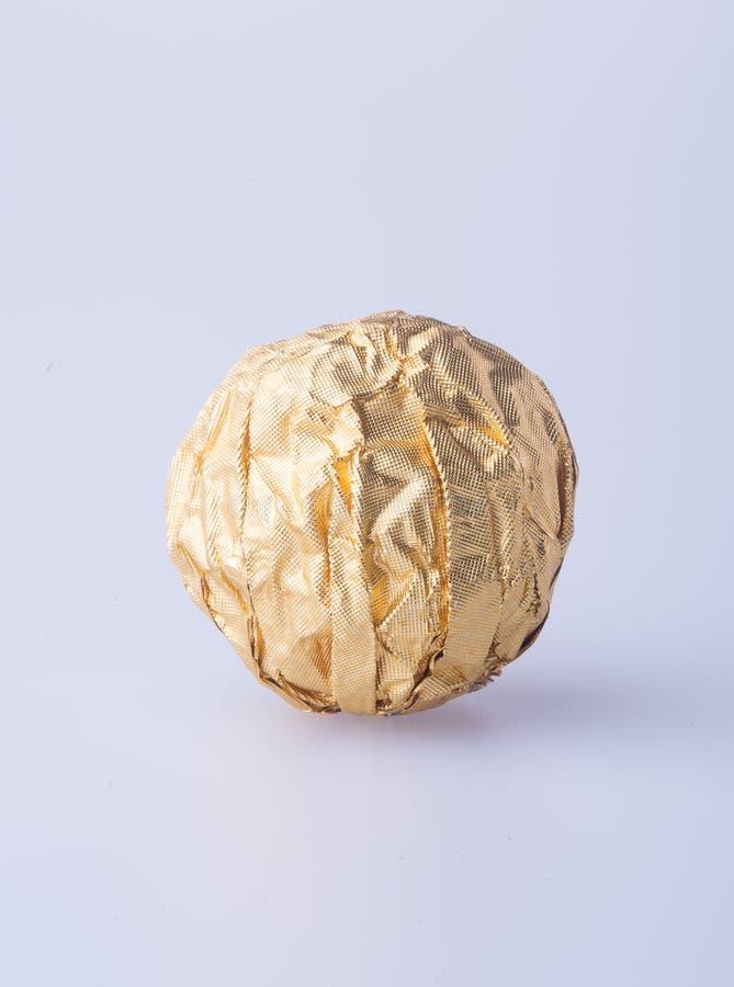 Шарик шоколада в бумаге сусального золота на предпосылке стоковые изображения rf