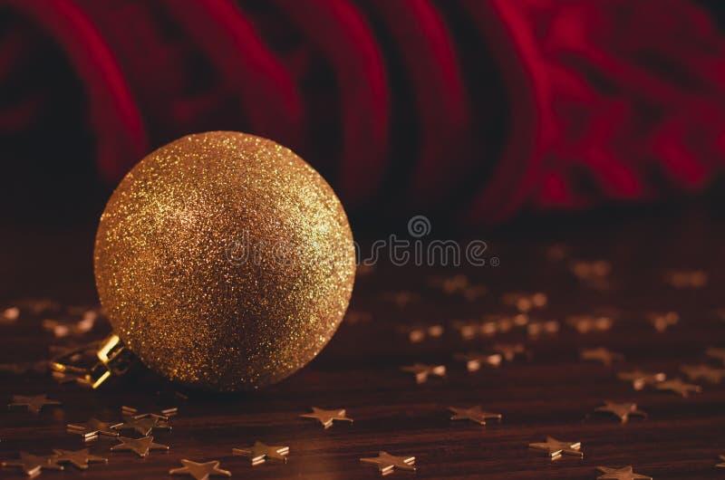 Шарик xmas золота лежит на таблице с небольшим confetti звезды и связанной красной ткани на предпосылке стоковое изображение rf
