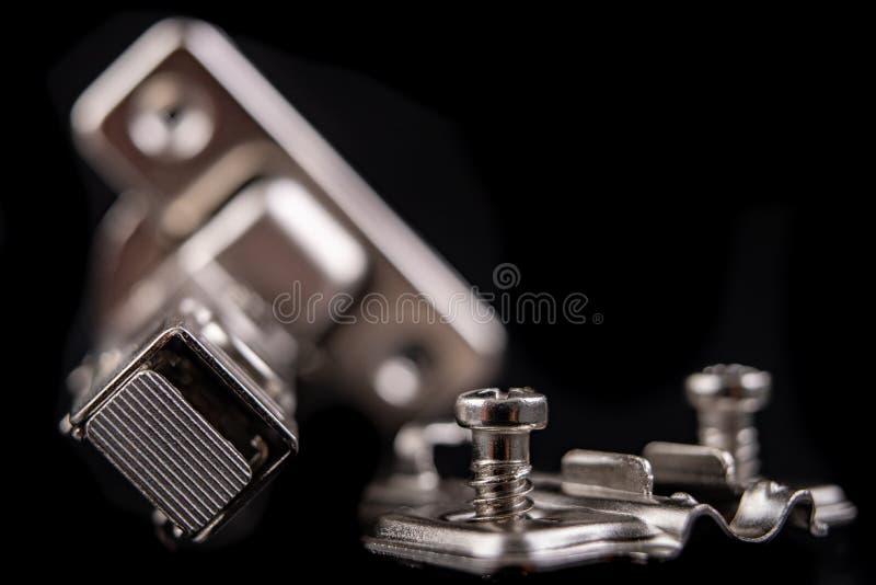 Шарниры мебели металла с гидравлическим тормозом Аксессуары мебели для продукции мебели на темной таблице стоковое фото rf