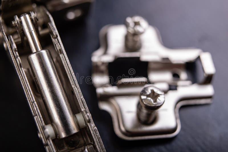 Шарниры мебели металла с гидравлическим тормозом Аксессуары мебели для продукции мебели на темной таблице стоковая фотография rf