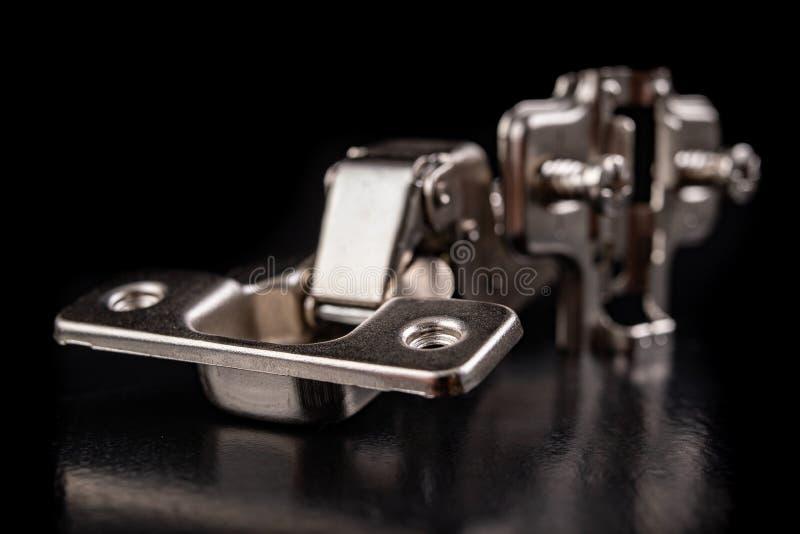 Шарниры мебели металла с гидравлическим тормозом Аксессуары мебели для продукции мебели на темной таблице стоковые изображения rf