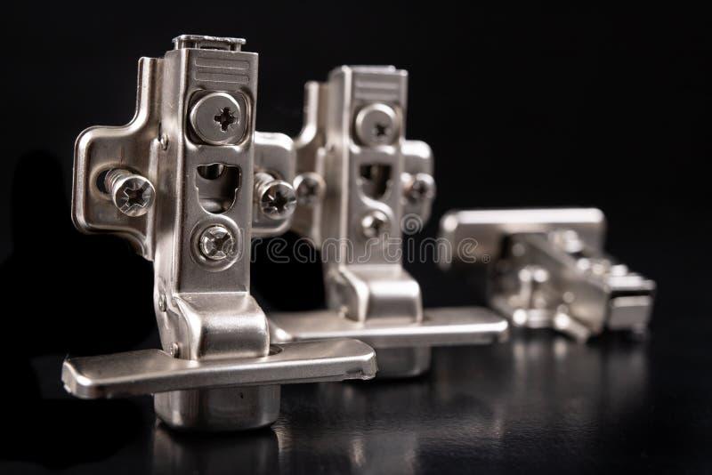 Шарниры мебели металла с гидравлическим тормозом Аксессуары мебели для продукции мебели на темной таблице стоковое изображение rf