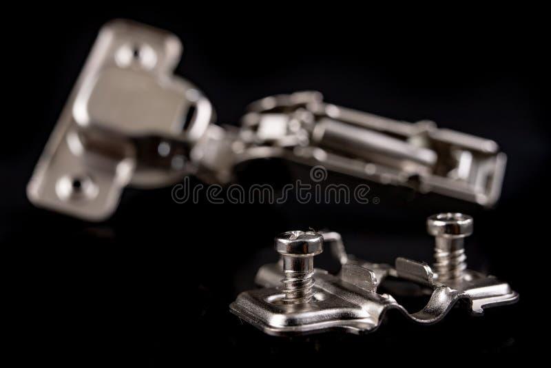 Шарниры мебели металла с гидравлическим тормозом Аксессуары мебели для продукции мебели на темной таблице стоковые фото