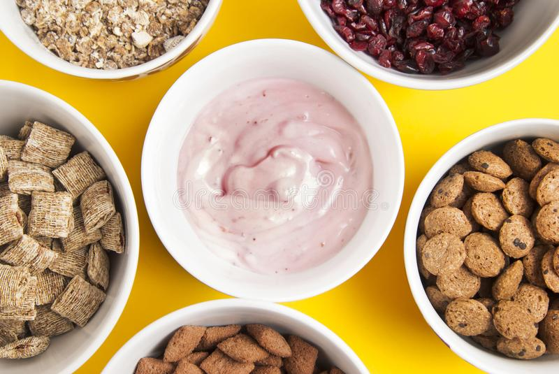 Шары всего muesli зерна, высушенных плодоовощей, granola и oatmeals аранжировали в круге Изолировано на желтой предпосылке Взгляд стоковые фото